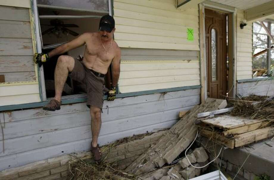 Chad Lavergne climbs out of a window as he searches through his ravaged Bridge City home in search of documents and personal items. Photo: Eric Gay, AP