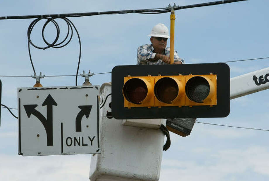 A utlity worker repairs a stoplight in Seabrook Tuesday. Photo: Mark Wilson, Getty Images