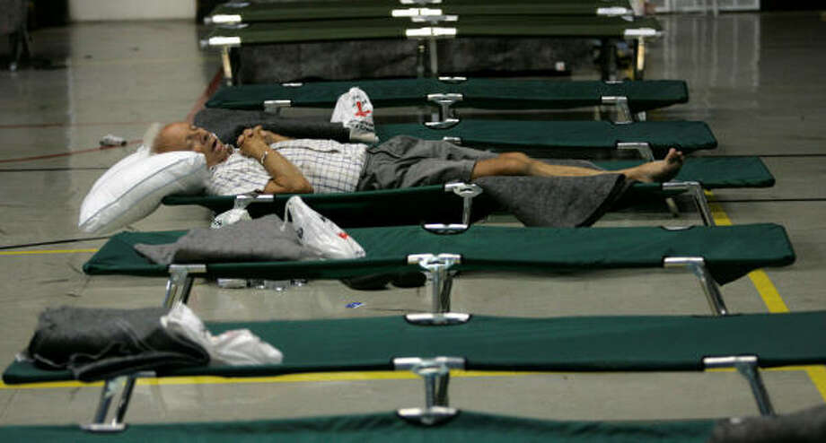A man rests on a cot at a Red Cross shelter inside Wooster Baptist Church in Baytown Tuesday. Photo: Marcio Jose Sanchez, AP