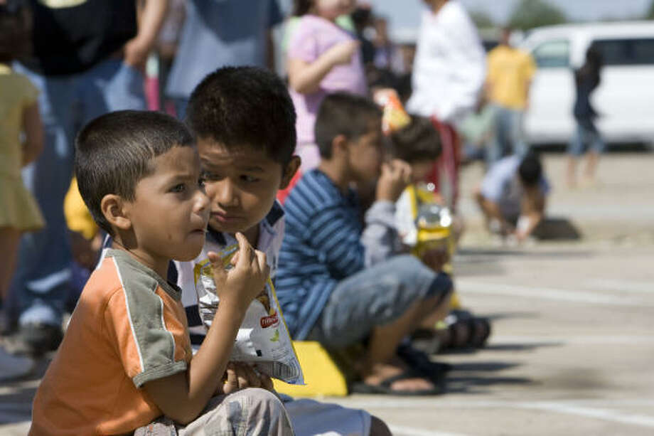 Luis Josue Villareal, left, and his cousin Aaron Rogelio Paredes eat potato chips as their family waits in line for lunch at the Salvation Army's Pasadena location. The organization was passing out food to families affected by Hurricane Ike. Photo: James Nielsen, Chronicle