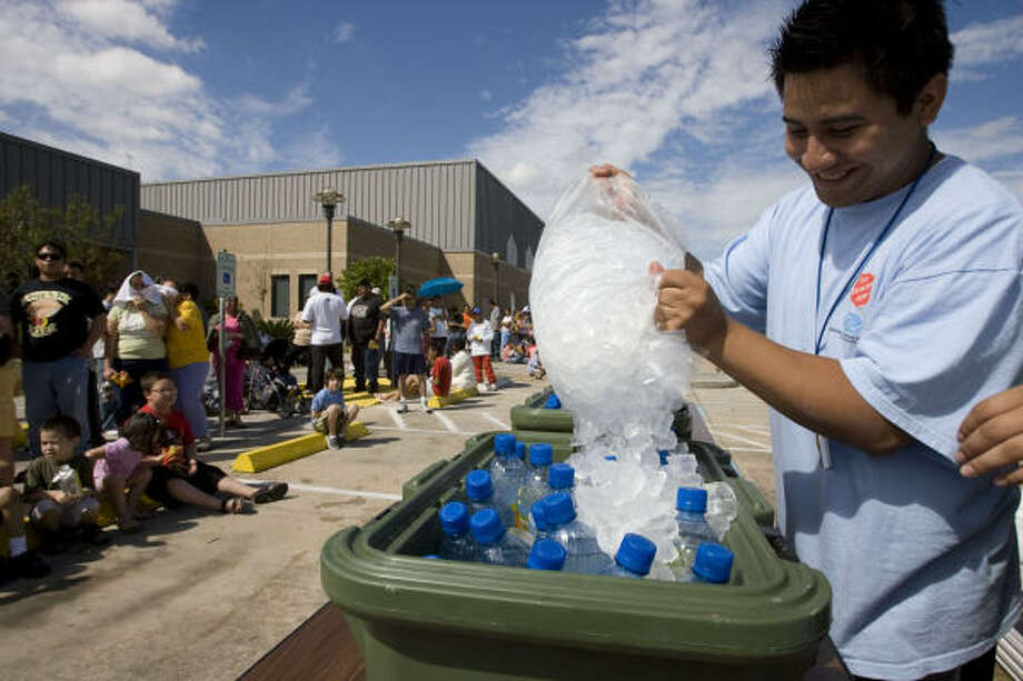 Volunteer Christian Baeza pours ice over drinks for lunch served to Pasadena residents by the Salvation Army. Photo: James Nielsen, Chronicle