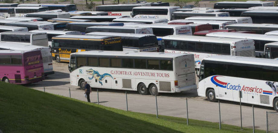 Buses to transport evacuees are staged in the Tully stadium parking lot on Dairy Ashford Road near Memorial Tuesday. Photo: Steve Ueckert, Chronicle
