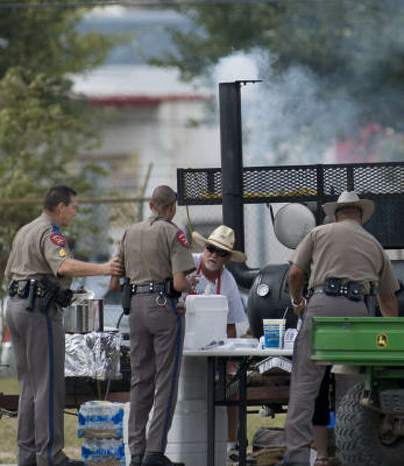 Volunteer Gordon Knight serves barbecue chicken to law enforcement officers at Tully Stadium Tuesday. Photo: Steve Ueckert, Chronicle