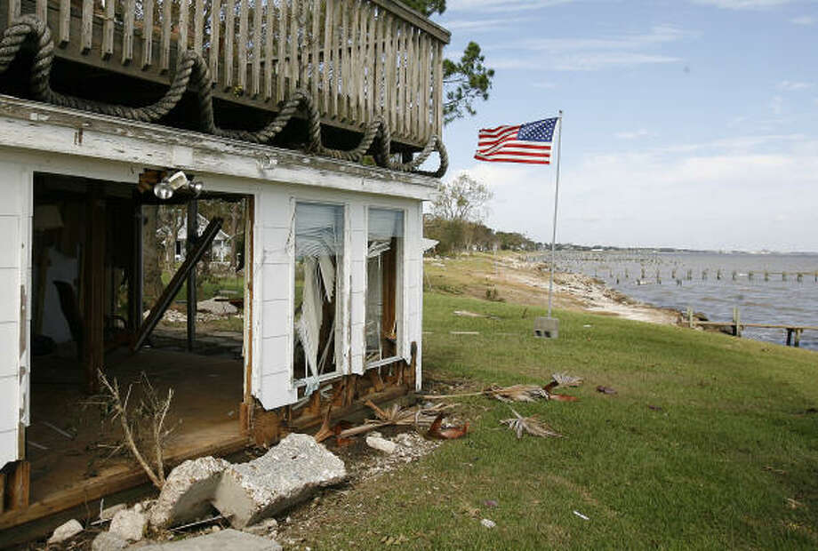 An American flag flies behind Terry Shingeltary's damaged bayfront home in Bacliff Tuesday. Photo: Kevin M. Cox, AP/The Galveston County Daily News