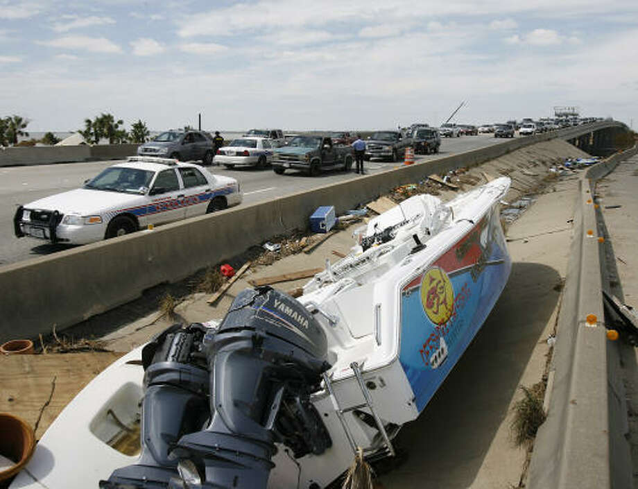 Vehicles wait to enter Galveston Island at a checkpoint on Interstate 45 South near Tiki Island, backed up for miles on Tuesday. A boat deposited by Hurricane Ike sits alongside the highway. Photo: Kevin M. Cox, AP/The Galveston County Daily News