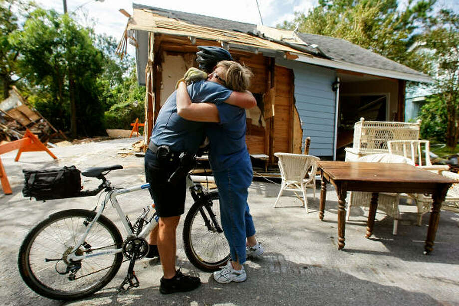 Seabrook police officer Jeff Galyean hugs his fourth grade teacher, Sue Harral, Tuesday in front of her home. which ended up in the middle of the street. Photo: Mark Wilson, Getty Images