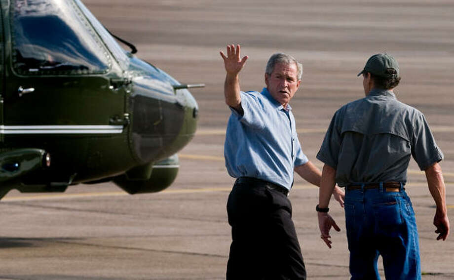 President George Bush waves as he walks with Governor Rick Perry to board a helicopter at Ellington Field for his tour of Hurricane Ike's devastation. Photo: Smiley N. Pool, Chronicle
