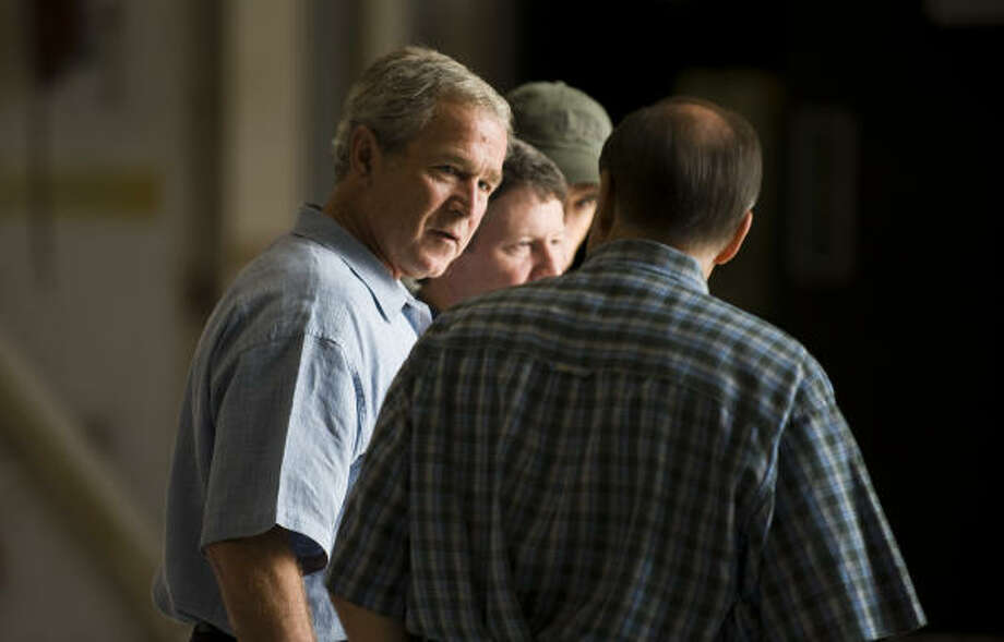 President George Bush talks with local officials after arriving at Ellington Field in Houston Tuesday. Photo: Smiley N. Pool, Chronicle