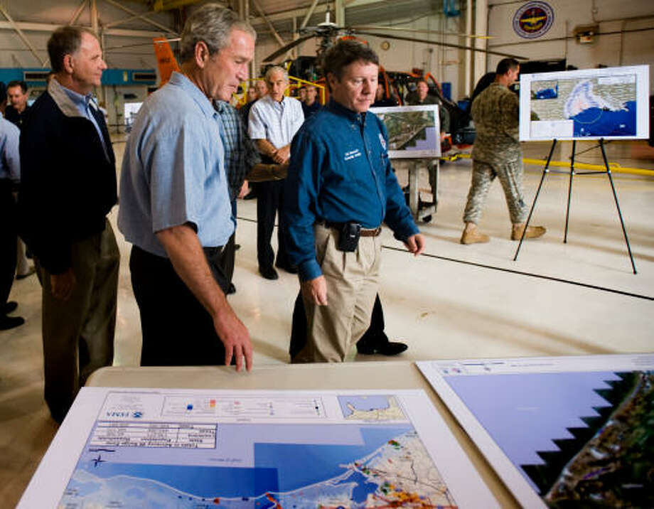 President George Bush looks over maps of the Texas coast with Harris County Judge Ed Emmett at Houston's Ellington Field Tuesday before boarding a helicopter for a tour of areas damaged by Hurricane Ike. Photo: Smiley N. Pool, Chronicle