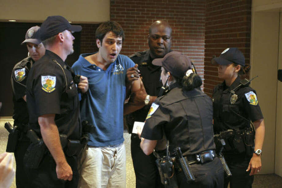 Student Andrew Meyer speaks with University of Florida police after being removed from a forum where Sen. John Kerry was speaking Monday in Gainesville, Fla. Photo: Andrew Stanfill, Independent Florida Alligator