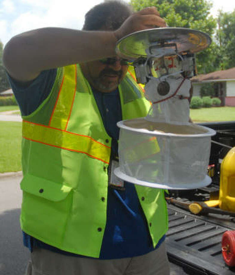 Oscar Salazar holds up a trap earlier this summer before placing it in a storm sewer to catch mosquitos. The Harris County Mosquito Control Division catches mosquitos all over the county and then takes them to the lab to be tested for West Nile and other diseases. Photo: Megan True, Chronicle File
