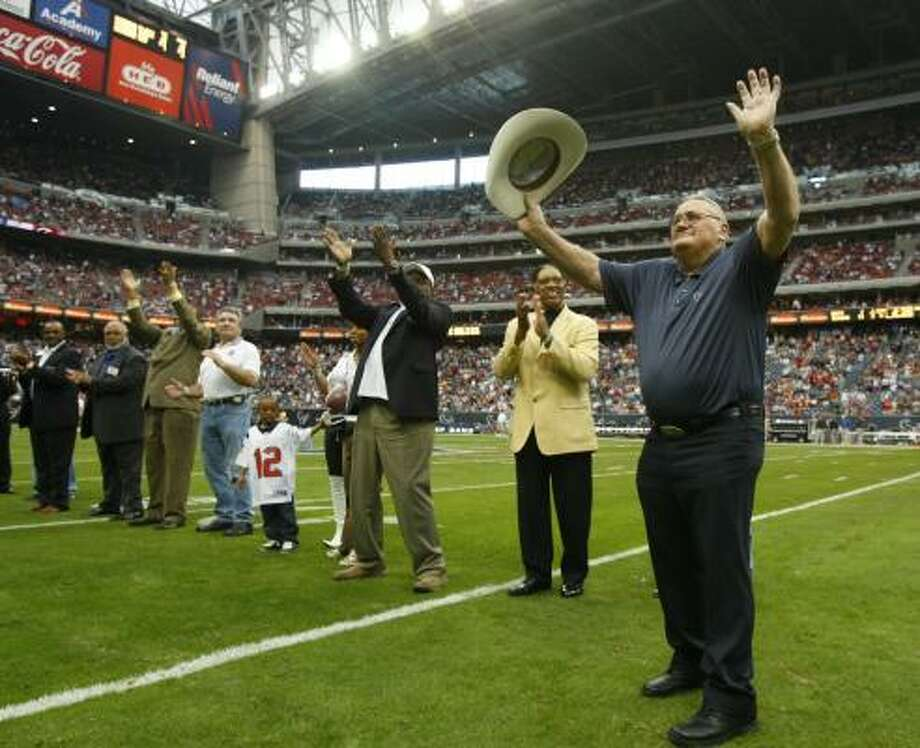 Bum Phillips, right, and members of the Oilers' Luv Ya Blue teams of the late '70s acknowledge the crowd during Sunday's halftime ceremony honoring them. Photo: BRETT COOMER, CHRONICLE