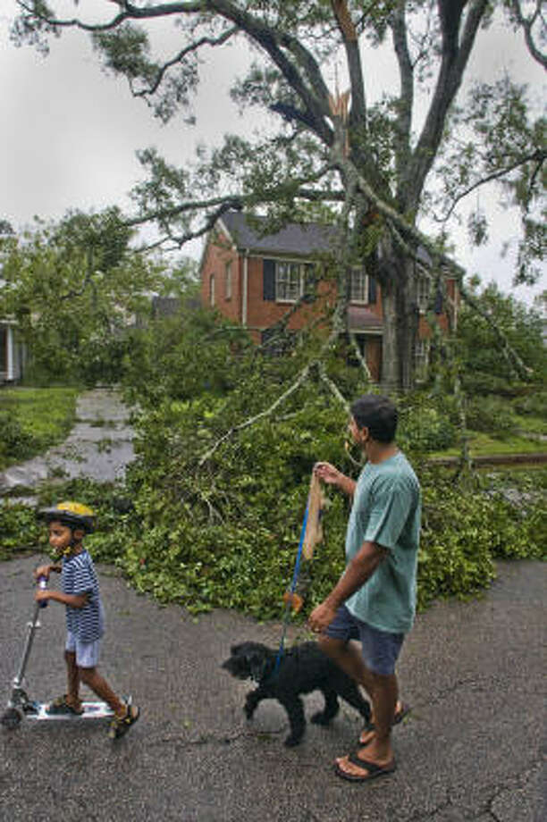 Upendra Marathi and his son, Pavan, 5, walk with their dog, Kirby, in a Houston neighborhood checking out damage from Hurricane Ike. Photo: Steve Ueckert, Associated Press