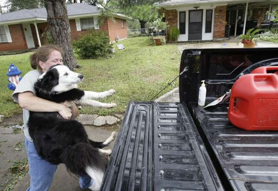 Chance Chatagnier loads her mother's dog, Baby, into the back of a pickup after getting the dog from her parents house in Bridge City after Hurricane Ike. Photo: Alex Brandon, Associated Press
