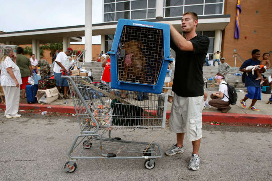 Chris Ragle and his dog, Diesel, arrive at an evacuation center in Galveston after his home was damaged by Hurricane Ike. Photo: Scott Olson, Getty Images