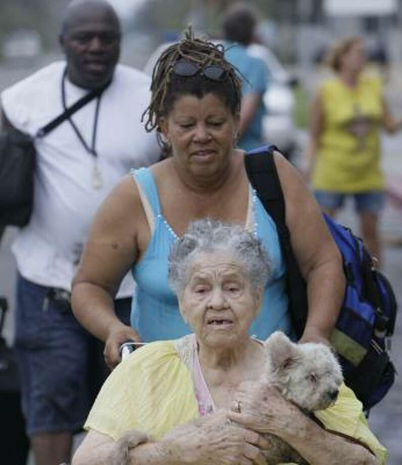 Aletia Skies pushes her mother, Emma Yarborough, and her dog, Pablo, in a wheelchair as her husband, Robert Sikes, carries their bags away from a shelter at Ball High School in Galveston. Photo: Melissa Phillip, Houston Chronicle