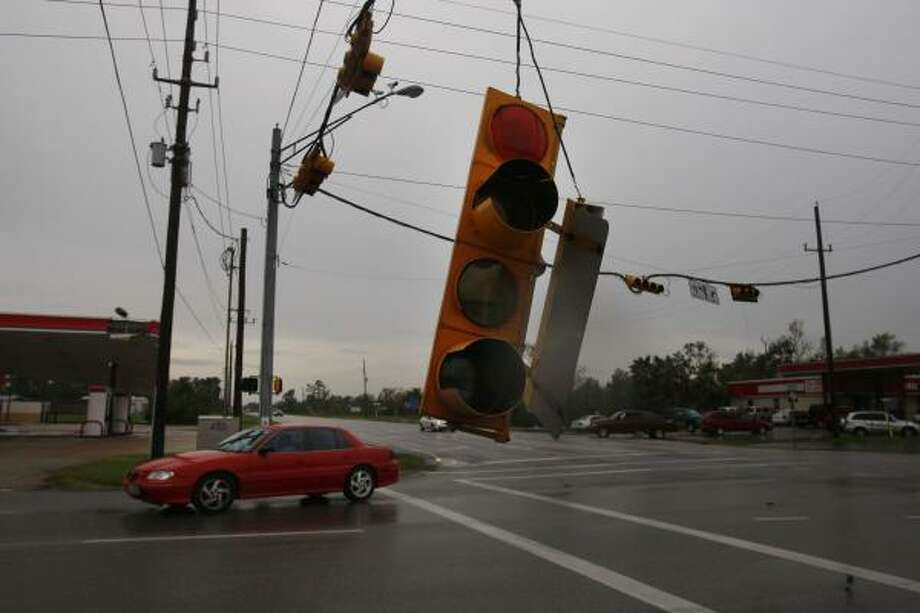 Light sign dangles by a wire along FM 518 in Hurricane Ike passed through the area on Sept. 13 in Pearland. Photo: Mayra Beltran, Houston Chronicle