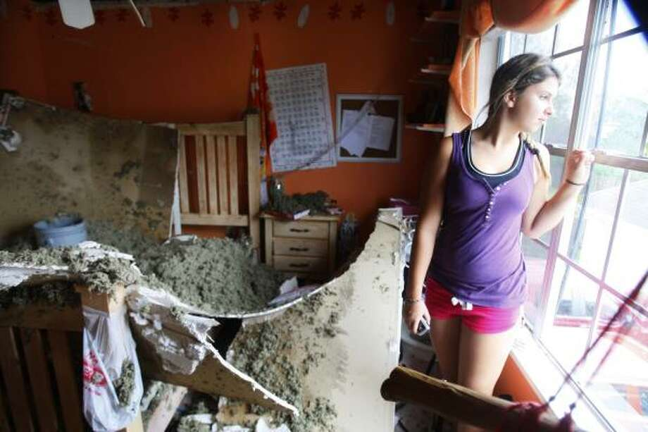 Alison Naquin, 14, roof in her bedroom caved in during the storm, but all her family was gathered in the game room in the Green Tee subdivision after Hurricane Ike on September 13, 2008 in Pearland. Photo: Mayra Beltran, Houston Chronicle
