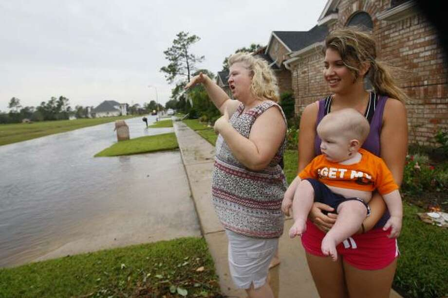 Debbie Naquin, daughter Alison Naquin, 14, and nephew Jet Decler, of Pearland, stand near the flooded street where cans cross high water in the Green Tee subdivision after Hurricane Ike on September 13, 2008 in Pearland. Photo: Mayra Beltran, Houston Chronicle