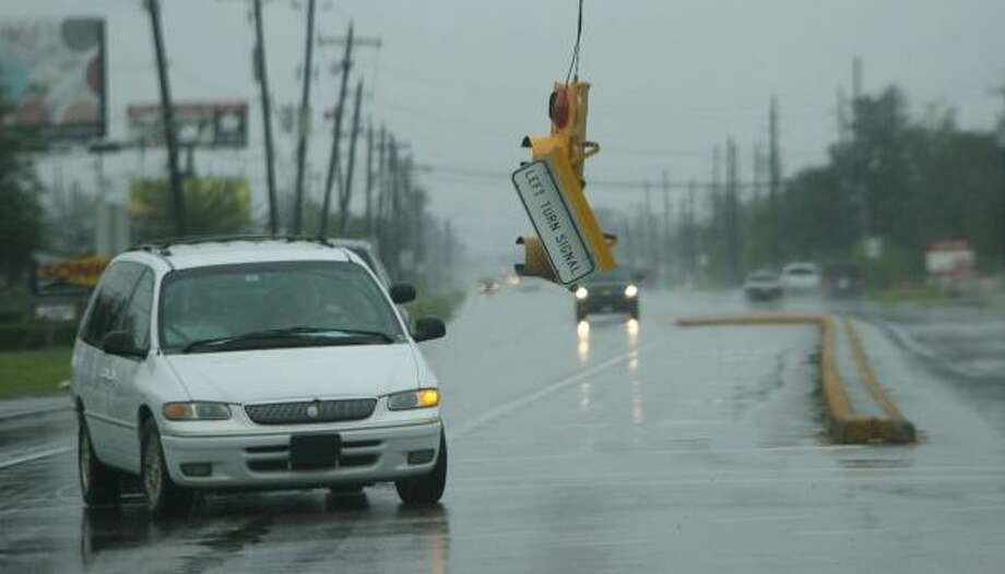 Light sign dangles by a wire along FM 518 in Hurricane Ike passed through the area on September 13, 2008 in Pearland. Photo: Mayra Beltran, Houston Chronicle