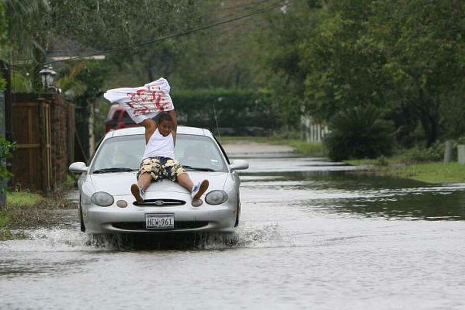 Eric Johnson, of Pearland, sits on the hood of his dad's car while crossing flooded alley in the Green Tee subdivision where flooding and damages can be seen after Hurricane Ike in Pearland. Photo: Mayra Beltran, Houston Chronicle