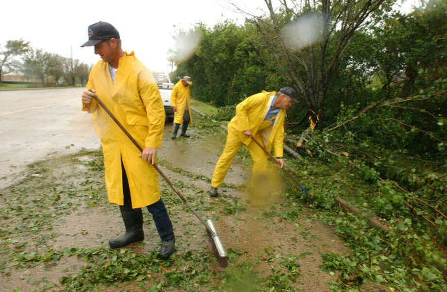 City of Pearland workers waste no time in getting limbs and trees off of the east of  518 in Pearland on early Saturday morning. Photo: Jimmy Loyd, For The Chronicle