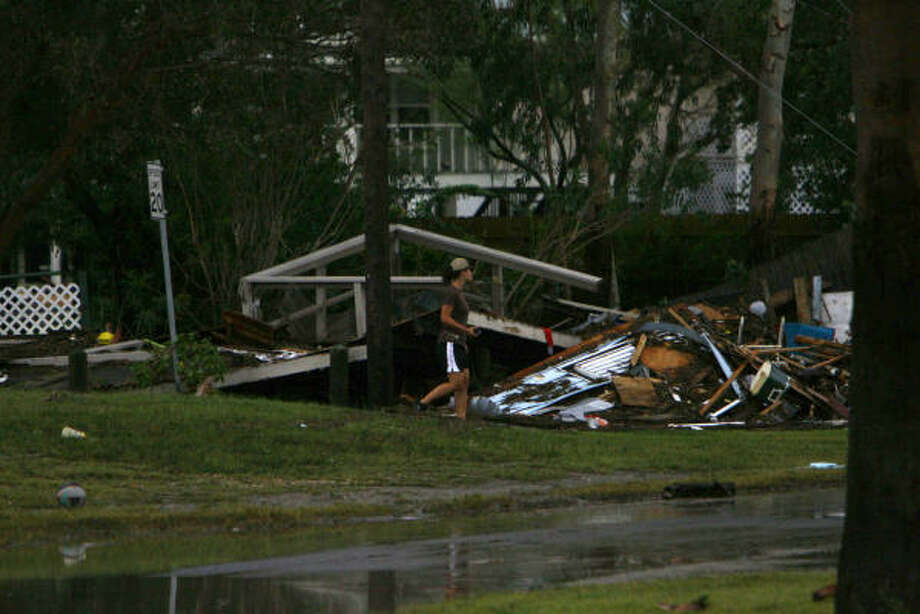 A woman walks by destroyed property Sunday in Hitchcock. Photo: Nick De La Torre, CHRONICLE