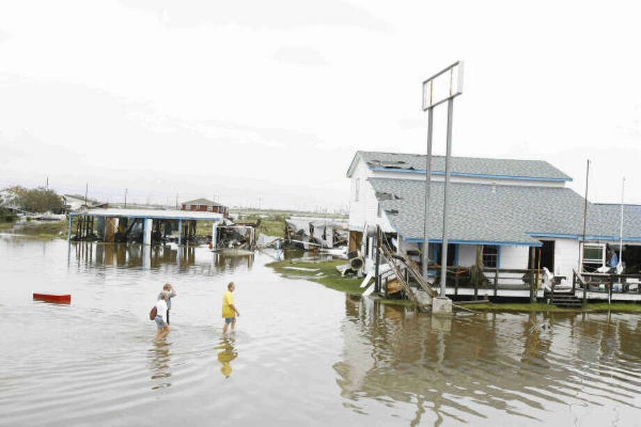 People wade through the high water near Louis Bait Shak in Hitchcock, Texas, on Sunday. Ike was the first major storm to directly hit a major U.S. metro area since Hurricane Katrina devastated New Orleans in 2005. Photo: Nick De La Torre, Chronicle