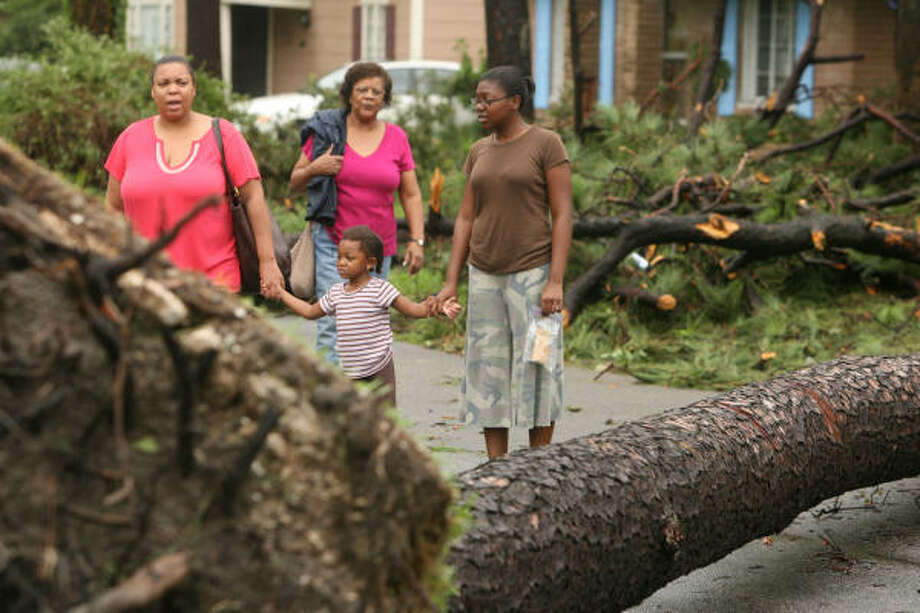 Hope Wright, left, walks with Fallon Wright, 3, Mia Wright, right and June Wright, back, as they check the damage out in Houston's Third Ward on Sunday. Photo: Billy Smith II, Chronicle