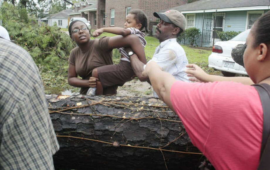 Mia Wright with the help of Donnie Moutra hands over Fallon Wright, 3, to Hope Wright as they check the damage out in their neighborhood in Houston's Third Ward on Sunday. Photo: Billy Smith II