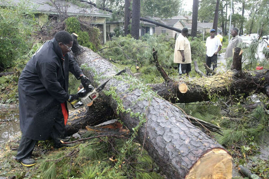 A Houston Police officer helps to clear huge pine trees that fell due to Hurricane Ike on Wentworth