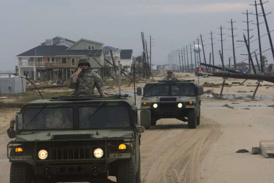Driving past the destruction left by Hurricane Ike, the Army National Guard C-Troop travels along FM 3005 to pick up two stranded women in the Pointe West neighborhood on Galveston's west side Sunday. Photo: Johnny Hanson, Chronicle