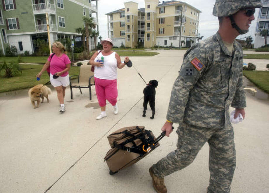 Beth Bishop, right, and her sister Mary Graham and their four dogs are picked up Sunday by National Guardsmen Cpl. Kenneth Carpenter after they were stranded in Galveston. Photo: Johnny Hanson, Chronicle
