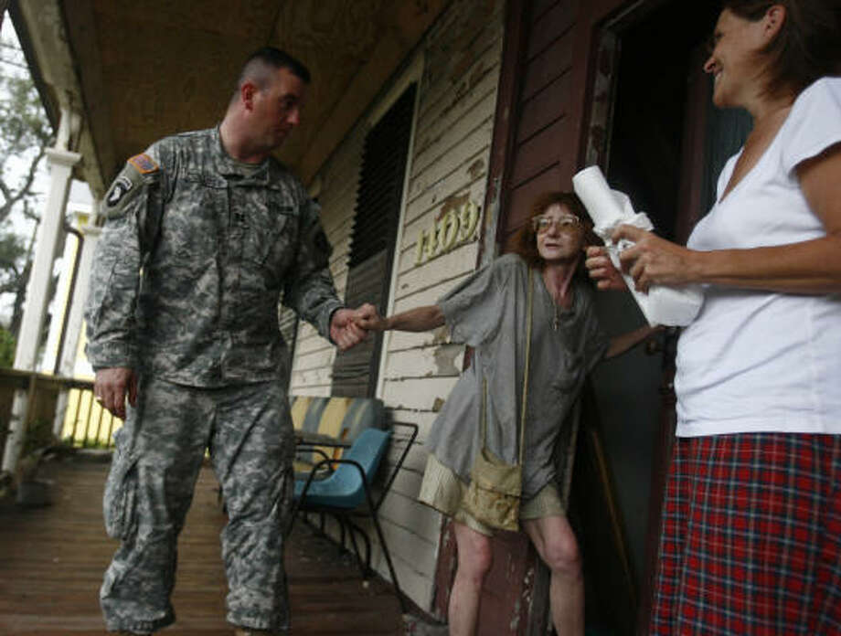 Sherry Jahn, who did not evacuate from Galveston, talks with her neighbor Terri Frankeny, right, and Texas Army National Guard Captain Adam Collett about her situation on Galveston Island on Sunday. Photo: Sharon Steinmann, Chronicle