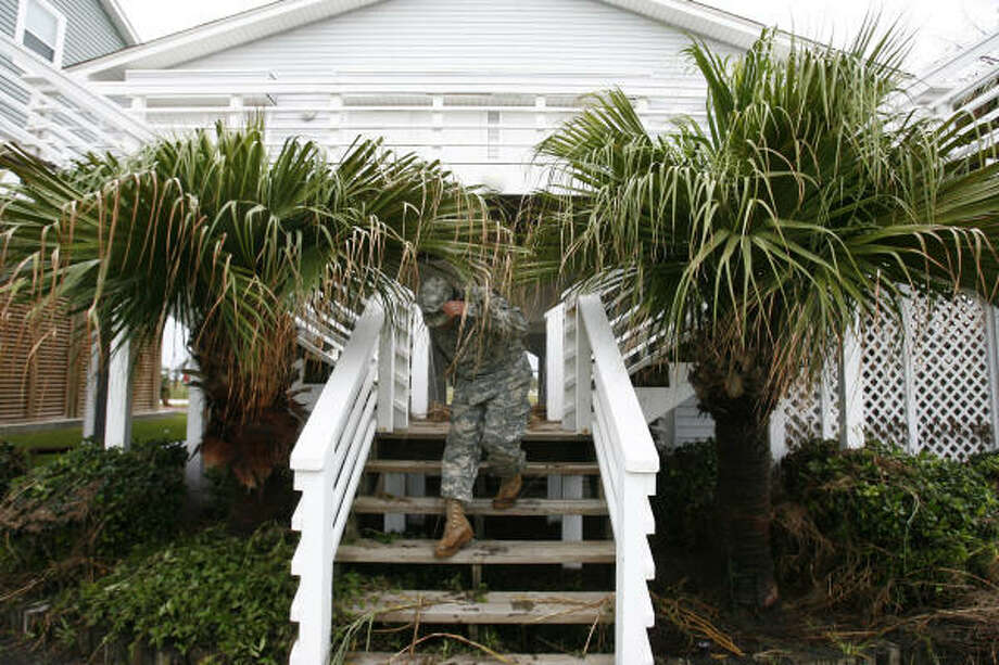 Spc. E4 Gerardo Mendez of the Texas Army National Guard conducts search and rescue operations door to door on west Galveston Island on Sunday. Most of the homes were empty. Photo: Sharon Steinmann, Chronicle