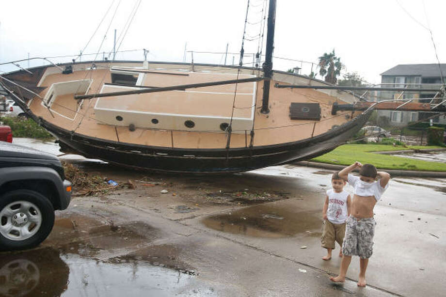 Dylan Guerra and his brother Fabian walk past a sailboat washed up outside their apartment complex during Hurricane Ike in Galveston, Texas. Photo: Scott Olson, Getty Images