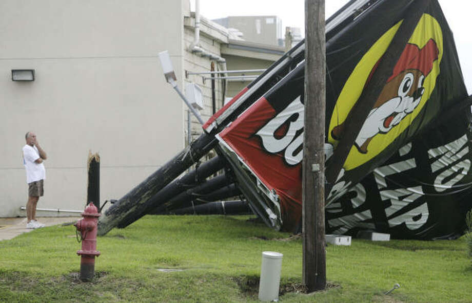 Buck Buchanan looks at a damaged billboard in Freeport, Texas, on Sunday. Photo: Julio Cortez, Chronicle