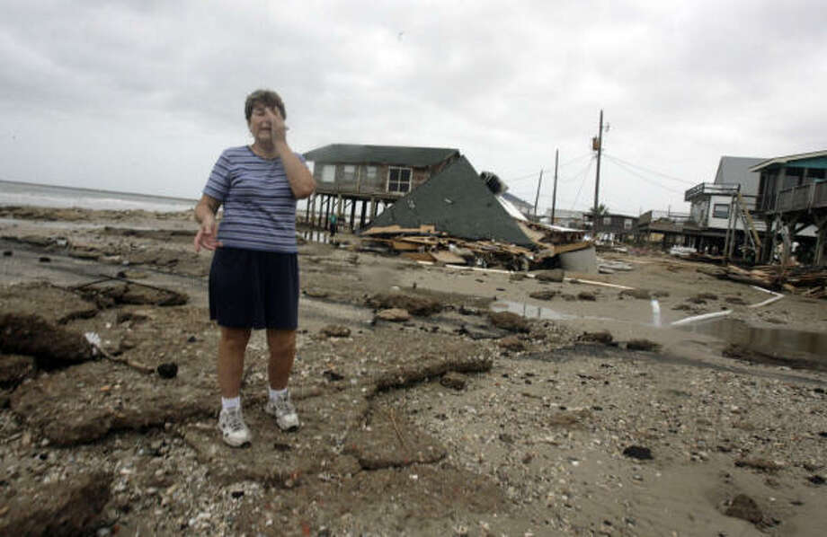 Betty Waters, of Lake Jackson, cries as she stands in front of what once was an eight room, eight bath house and talks about the loss of a 50-foot boat that sank during Hurricane Ike. Photo: Julio Cortez, Chronicle