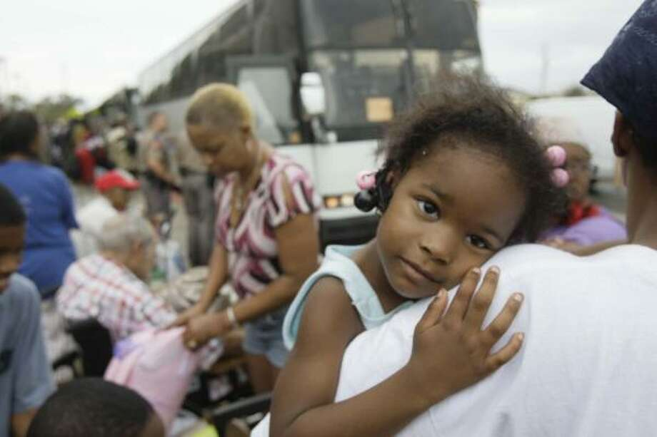 Derica Williams, 4, waits with her family to board an evacuation bus at Galveston's Ball High School on Sunday. Photo: Melissa Phillip, AP