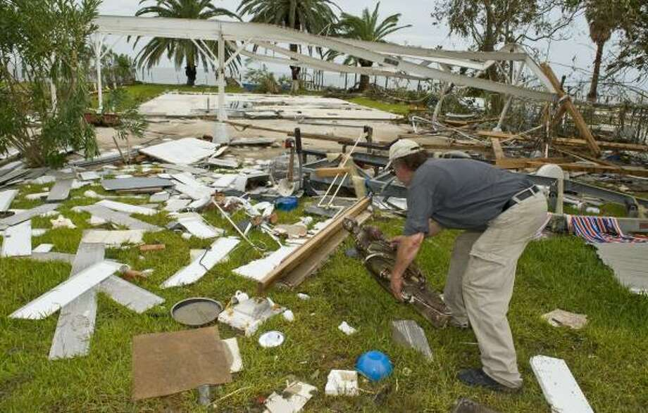Leo Mirok picks up a carving in front of the remains of his home Sunday in San Leon, Texas. Photo: Dave Einsel, Getty Images
