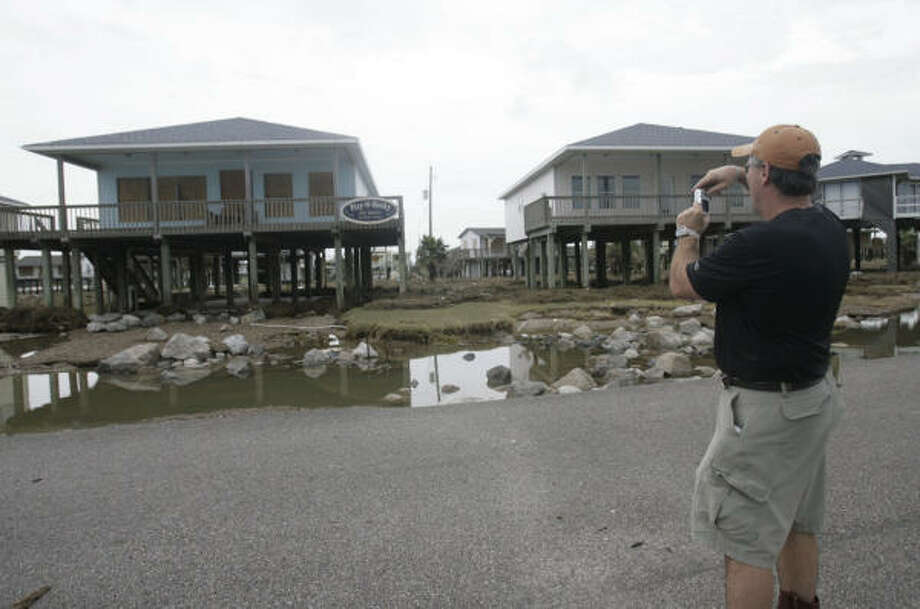 Andy Cason, of Lake Jackson takes a photo of his beach-front property on Surfside Beach, which he bought a week before Hurricane Ike rolled through the Texas coast. Photo: Julio Cortez, Chronicle