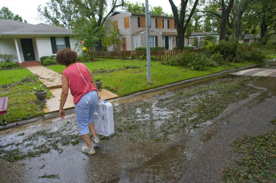 Sarah Kasbidi walks Sunday to her home on Southgate Boulevard  with a borrowed fan and an extension cord. Photo: Steve Ueckert, Chronicle