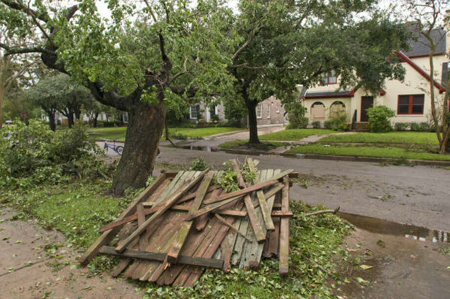 Fencing downed by Hurricane Ike is stacked Sunday near downed trees and branches in the Southgate neighborhood near Rice University. Photo: Steve Ueckert, Chronicle