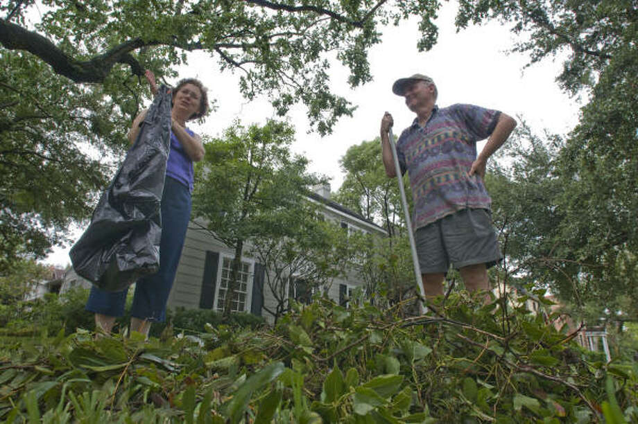 Marsha and Kevin Hennigan rake leaves and twigs that cover their yard Sunday in the Southgate neighborhood near Rice University. Photo: Steve Ueckert, Chronicle