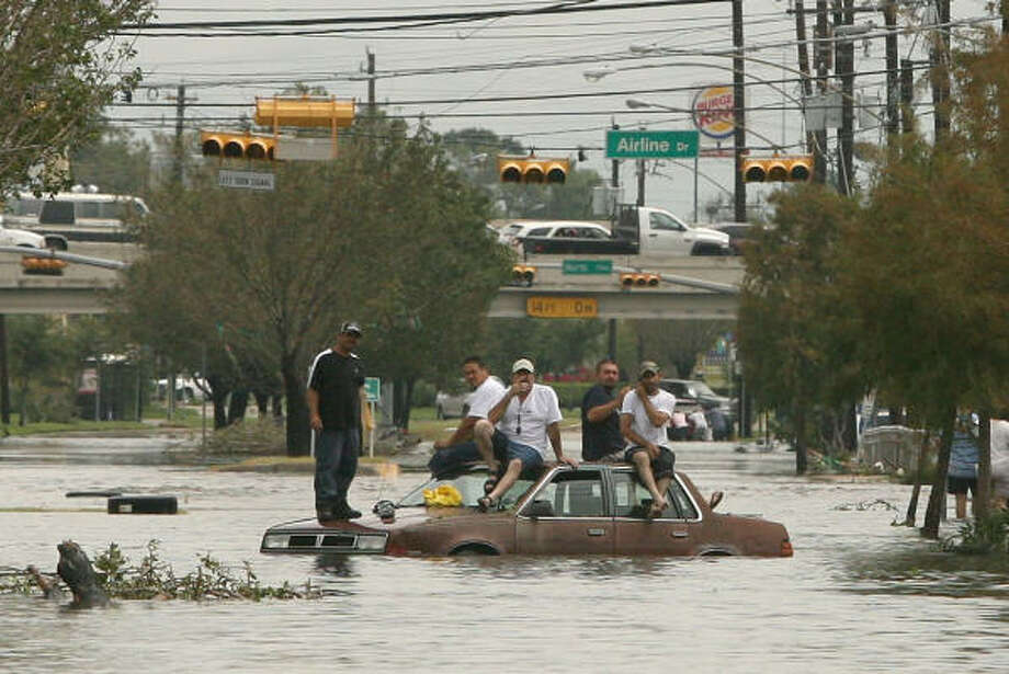 Pedestrians take refuge from the floodwaters on Airline on top of a half-submerged car. Photo: Bill Olive, For The Chronicle