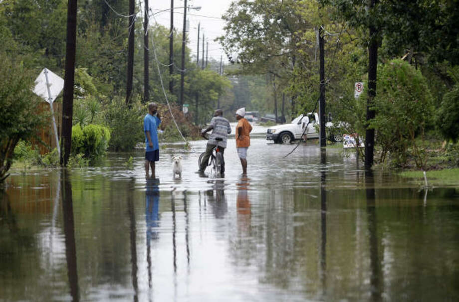 Residents that live in Independence Heights talk to each other as floodwaters start to recede Sunday in the area north of Interstate 610. Photo: Karen Warren, Chronicle