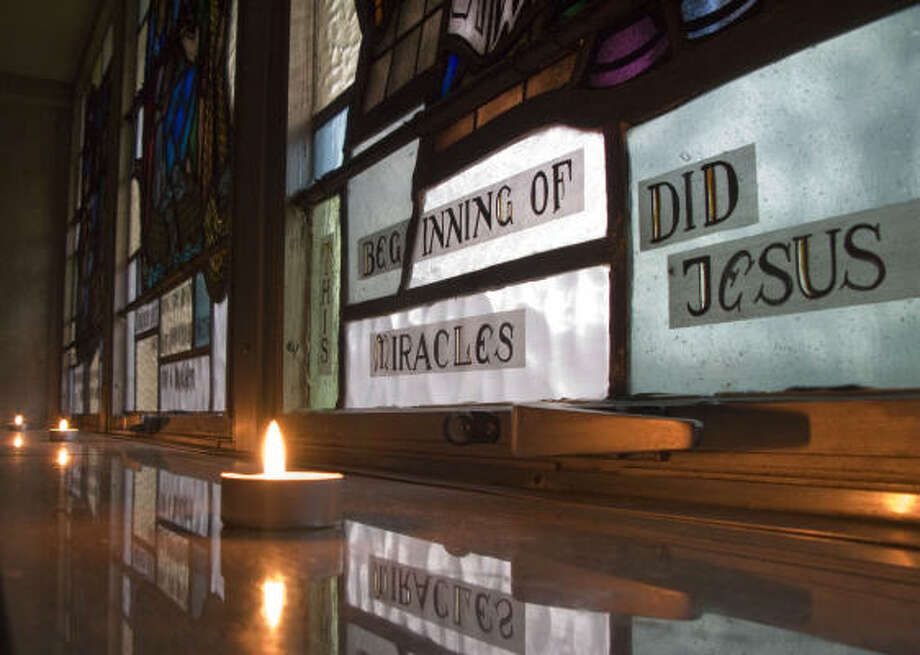 Candles and stained glass windows provide the only light at St. Vincent de Paul Catholic Church on Holcombe at Buffalo Speedway on Sunday. Photo: Steve Ueckert, Chronicle
