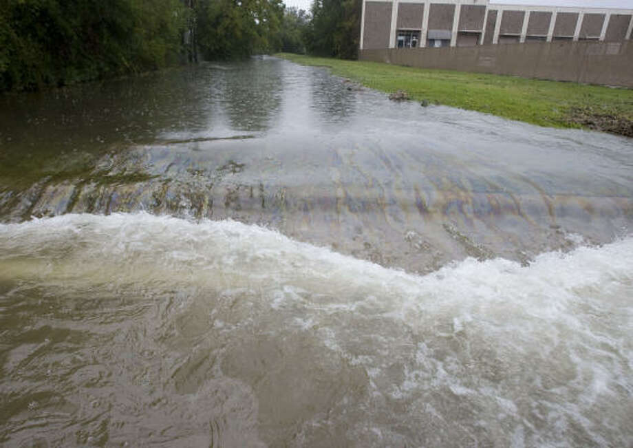 A petroleum product that may be gasoline mixes floodwaters in a bayou near the Westview Terrace subdivision Sunday after Hurricane Ike moved through the area. Photo: James Nielsen, Chronicle