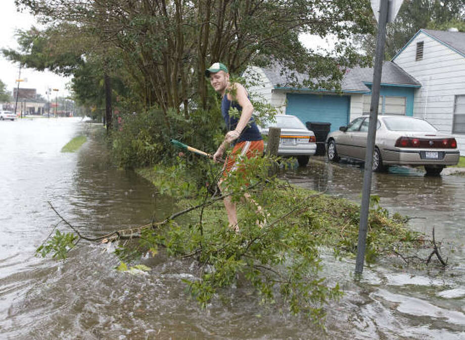 Justin Grant clears debris from a storm drain in the Westview Terrace subdivision Sunday after Hurricane Ike moved through the area. Photo: James Nielsen, Chronicle