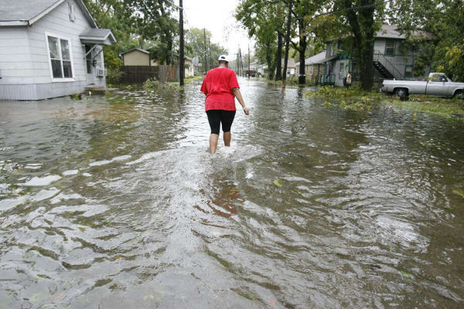 Exie Jarmon walks through the flooded street of her home on Cortland Street Sunday in Independence Heights north of Interstate 610, where waters from overnight rains flooded the area around Yale and Main. Photo: Karen Warren, Chronicle
